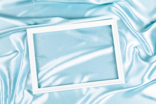 Cadre en bois blanc vide sur un beau mur de satin de soie bleu clair. vue de dessus