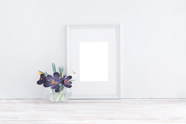 Cadre en bois blanc vide et fleurs dans un vase sur fond blanc avec espace de copie. maquette.