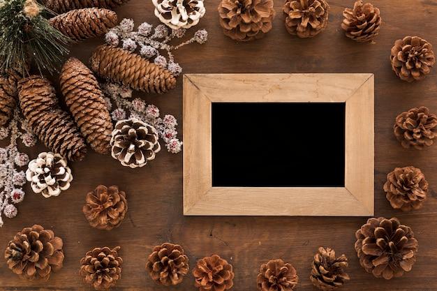 Cadre en bois avec des cônes sur la table
