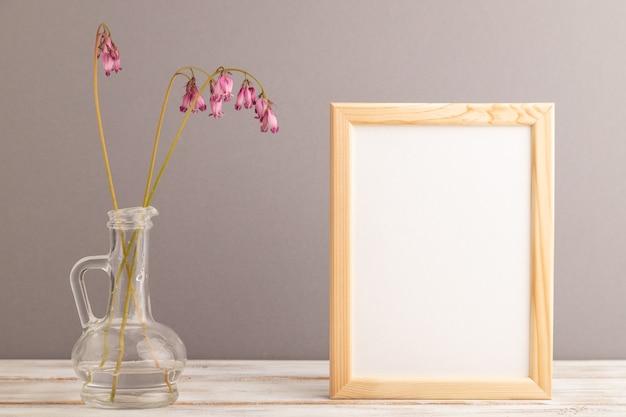 Cadre en bois avec dicentra rose, coeur brisé en verre sur fond pastel gris. vue de côté