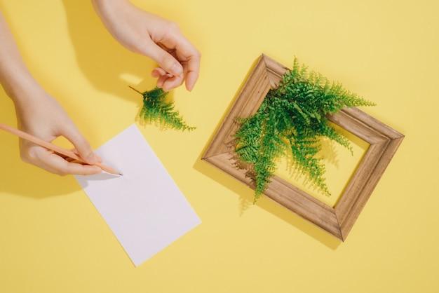 Cadre en bois avec feuilles et note vierge