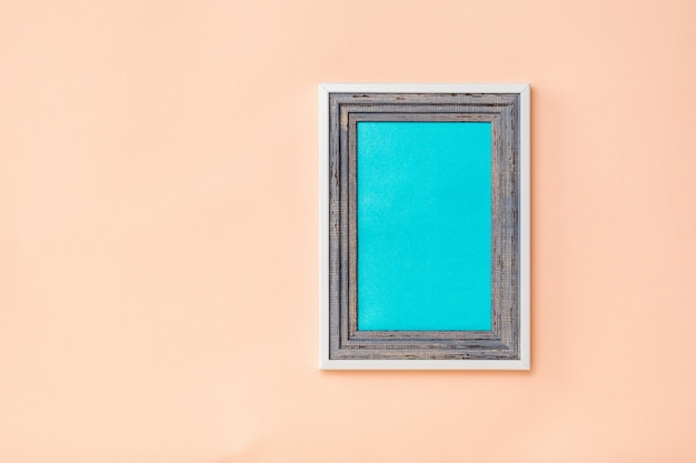Cadre en bois avec fond bleu à l'intérieur de la literie sur fond de corail. la tendance des couleurs. minimalisme. arrière-plan pour le placement de photos.