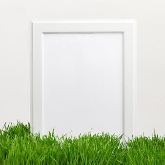 Cadre en bois sur l'herbe naturelle verte. humeur printanière. concept de vacances de pâques. copiez l'espace.