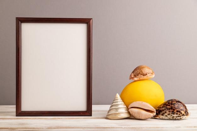Cadre en bois avec melon, coquillages sur fond pastel gris. vue latérale, copiez l'espace. tropical