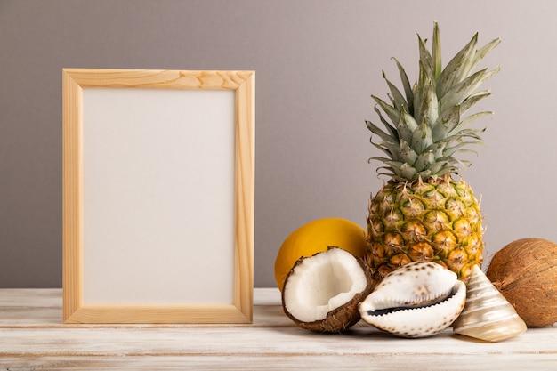 Cadre en bois avec melon, noix de coco, ananas, coquillages sur fond pastel gris.copier l'espace.