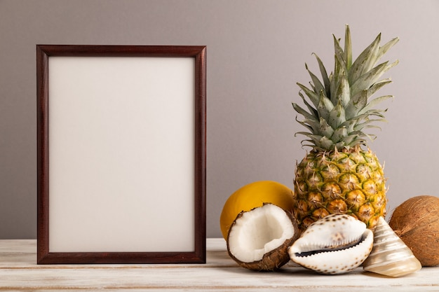 Cadre en bois avec melon, noix de coco, ananas, coquillages sur fond pastel gris. vue de côté,