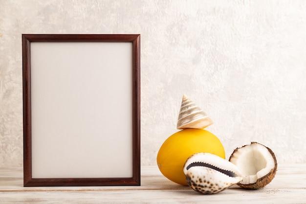 Cadre en bois avec melon, noix de coco, coquillages sur fond de béton gris. vue latérale, espace de copie