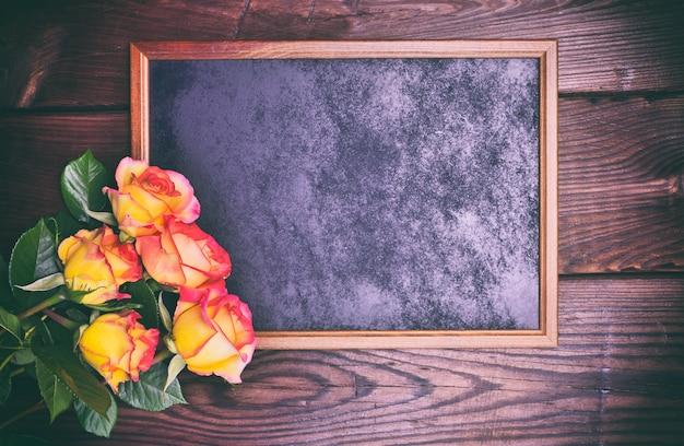 Cadre en bois noir à côté d'un bouquet de roses jaunes