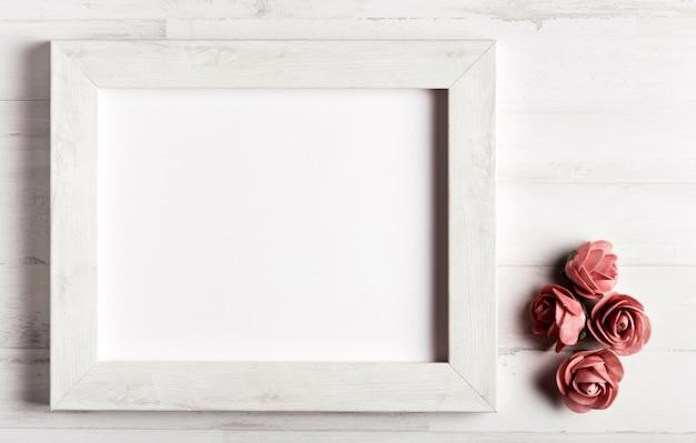 Cadre en bois avec des roses à côté