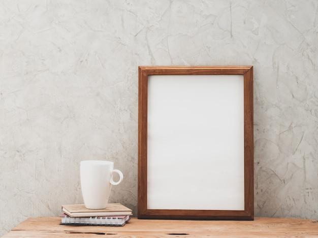 Cadre en bois de teck et tasse à café blanche maquette sur table grunge