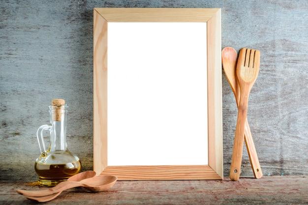 Cadre en bois vide avec fond blanc isolé et ustensiles de cuisine