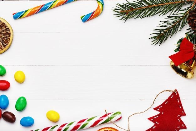 Cadre de bonbons et autres articles de noël sur fond de bois blanc avec un espace réservé au texte