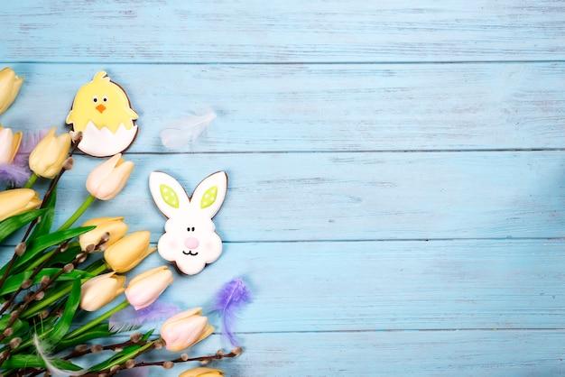 Cadre de bonbons pour célébrer pâques. pain d'épice en forme de lapin de pâques, poulet et tulipes