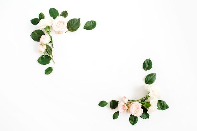 Cadre de bordure avec des boutons de fleurs roses beiges et des feuilles vertes isolées sur fond blanc. mise à plat, vue de dessus