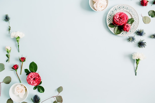 Cadre de bordure de fleurs composé de roses rouges et beiges, d'œillets blancs et de branches d'eucalyptus sur fond bleu pastel pâle. mise à plat, vue de dessus
