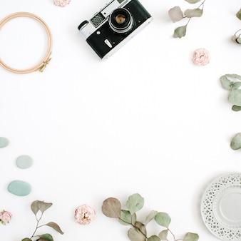 Cadre de bordure plate laïque avec appareil photo rétro, branches d'eucalyptus, plaque sur blanc