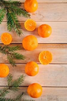 Cadre en branches de sapin et mandarines sur un bois