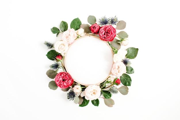 Cadre de broderie avec des boutons de fleurs roses rouges et beiges isolés sur fond blanc. mise à plat, vue de dessus
