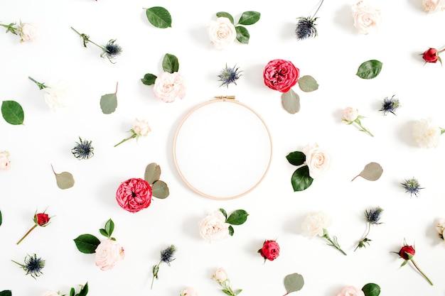 Cadre de broderie avec des boutons de fleurs roses rouges et beiges. mise à plat, vue de dessus