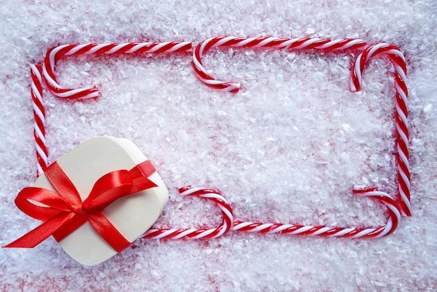 Cadre de canne en bonbon cadeau de noël sur la neige
