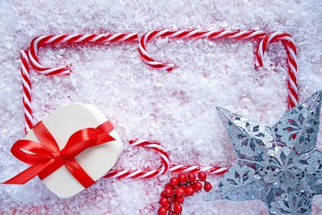 Cadre de canne à sucre de noël sur la neige