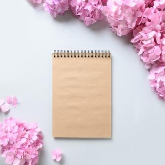 Cadre carré avec carnet de croquis et fleurs d'hortensia rose sur fond gris. carte de voeux de fête des mères avec espace de copie. vue de dessus.