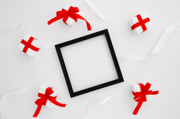 Cadre carré noir avec deux cravates rouges et des cadeaux de noël sur fond blanc