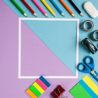 Cadre carré avec papeterie sur fond bleu et violet. mise à plat.
