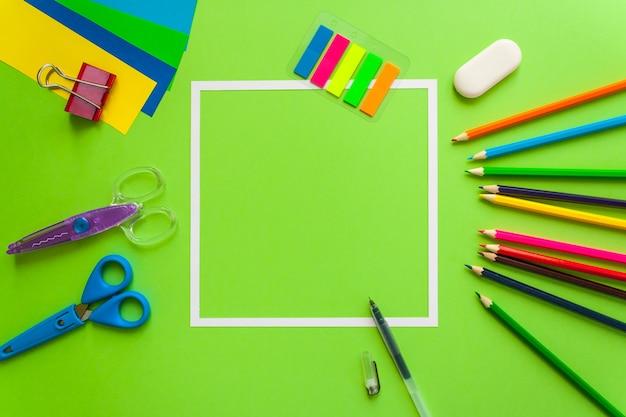 Cadre carré avec papeterie à plat sur fond vert