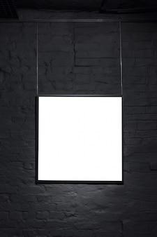 Cadre carré vide sur mur de briques noires. affiche d'espace vide ou cadre d'art en attente d'être rempli. fond de cadre noir carré