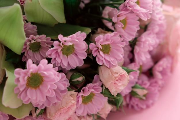Cadre de chrysanthèmes violets et roses, orchidée et différentes fleurs sur fond rose.