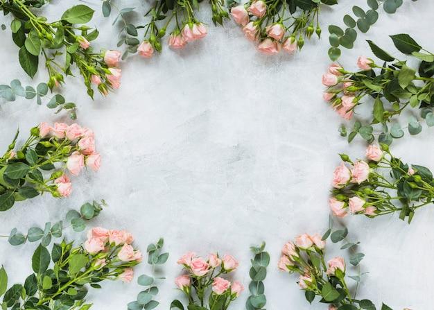 Cadre circulaire fait avec bouquet de roses sur fond de béton