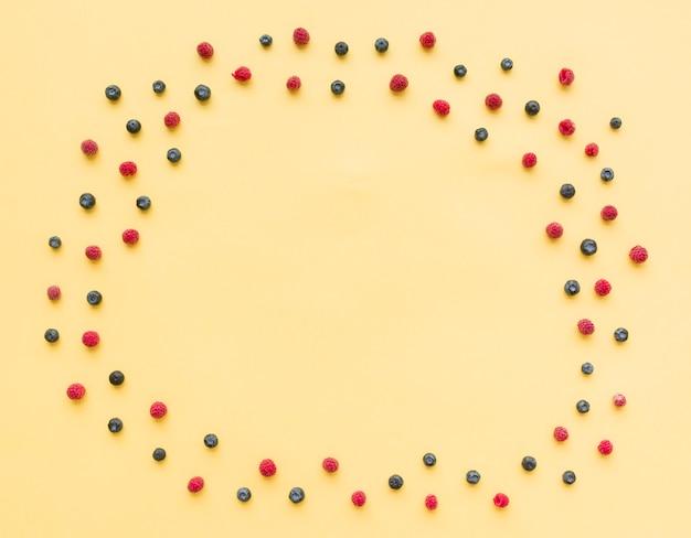 Un cadre circulaire vide fait avec des bleuets et des framboises sur fond beige
