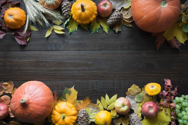Cadre de citrouille et d'érable feuilles sur une planche en bois avec motif automne vue de dessus