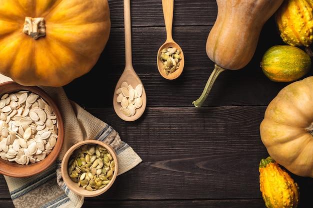 Cadre de citrouilles de différentes tailles sur un fond en bois. une assiette et un bol de graines de citrouille sont posés sur un torchon. deux cuillères à graines. vue de dessus. copiez l'espace.