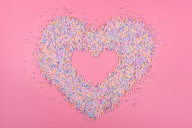 Cadre coeur en boules de couleur pastel sur mousse de polystyrène ou polystyrène rose
