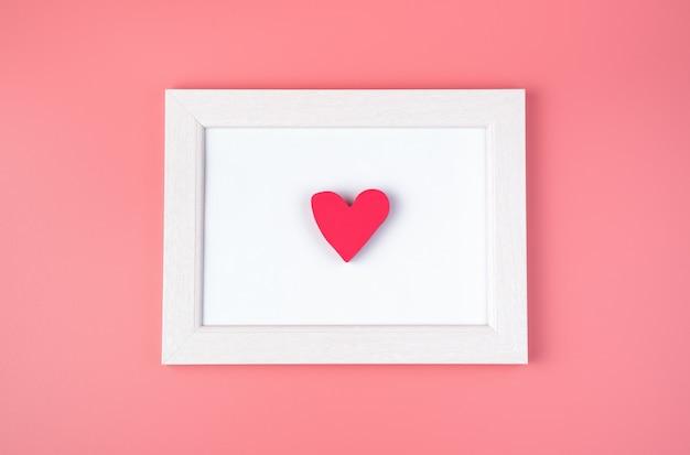 Cadre coeur sur fond rose.
