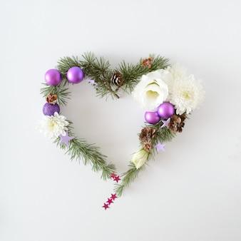 Cadre coeur de noël fait d'articles de noël naturels, boules de noël, fleurs, pommes de pin et autres décorations. espace pour le texte.
