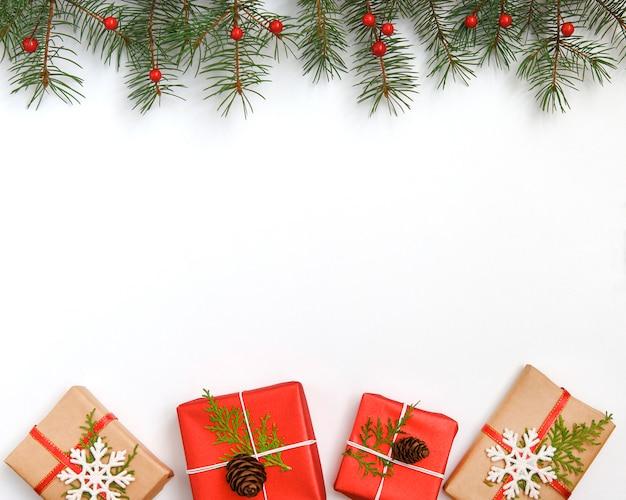 Cadre composé de cadeaux de noël, de branches de pin sur fond blanc.