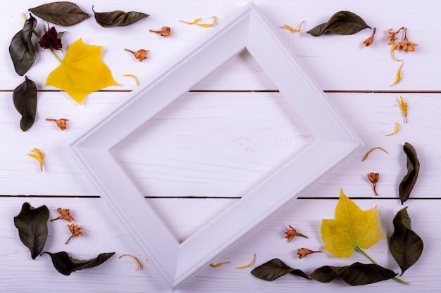Cadre composé de fleurs séchées, feuilles séchées sur un fond en bois blanc.