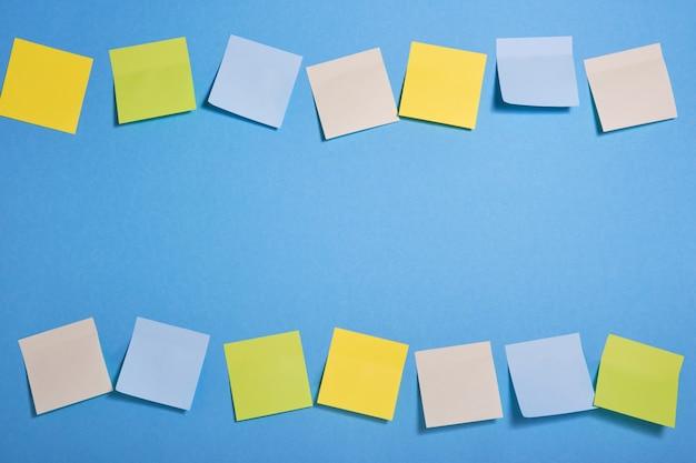 Cadre composé de notes autocollantes de couleur vive sur fond bleu, mise au point sélective