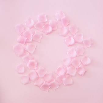 Cadre composé de pétales de roses roses sur fond rose