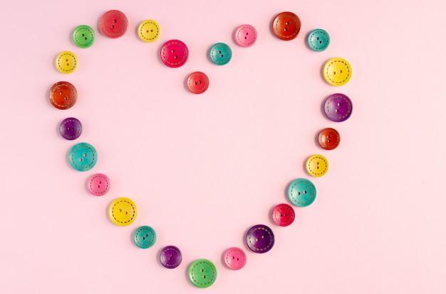 Cadre de composition de boutons de couture couleur sur fond rose.