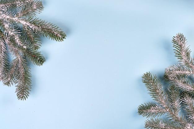 Cadre de composition de noël composé de branches de sapin sur bleu