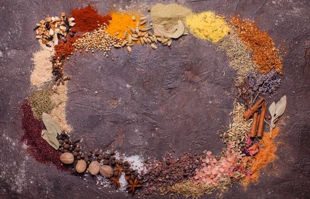 Cadre de composition à plat de diverses épices sur fond d'ardoise brune, vue de dessus