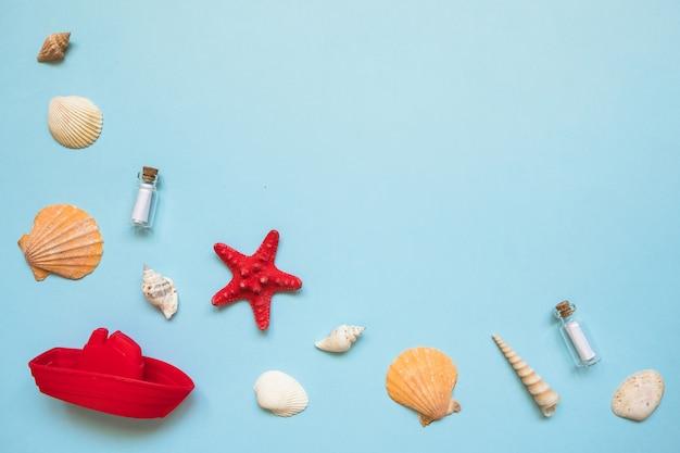 Cadre avec coquillages, étoile de mer rouge et bateau jouet sur la mer bleue