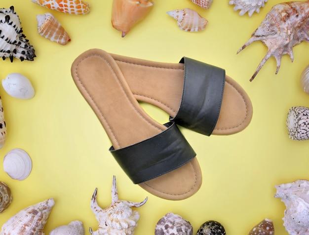 Cadre de coquillages sur fond jaune avec une paire de sandales au centre