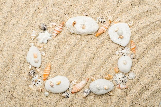 Cadre en coquillages et pierres sur sable beige de mer