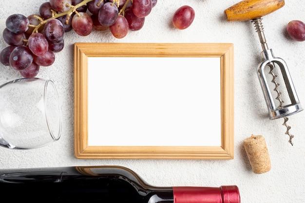 Cadre à côté de la bouteille de vin et des raisins