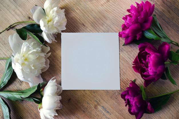 Cadre de couleurs blanches et lilas pivoine sur une planche de bois avec carte de voeux blanche vierge. texture de fleurs lay plat, vue de dessus.